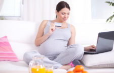 Young pregnant woman buying on internet