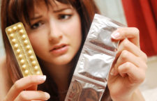 A girl in her bedroom looking at condoms and contraceptive pills and doesnt know which she should use.