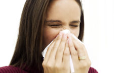 Young Woman Sneezing into a Handkerchief --- Image by © Royalty-Free/Corbis